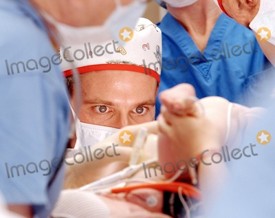 Photo - Plastic Surgeon John Gross, M.D., FACS of Childrens Hospital Los Angeles, performs a delicate procedure at the beginning of a historic, marathon surgery to separate conjoined 9-month-old twin girls at the hospital beginning 9/10/03. (HO/Photo by Bob Riha, Jr./CHLA)