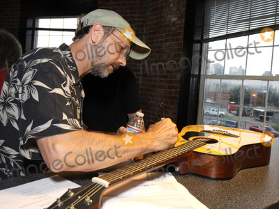 Jeff Taylor, Pete Huttlinger Photo - July 26, 2011 - Nashville, TN - Jeff Taylor autographs a guitar later auctioned off. Artists, musicians and songwriters came together at Mercy Lounge to help raise funds for Pete Huttlinger, a widely respected guitarist and Nashville studio artist.  Huttlinger has a congenital heart disease and is in need of a heart transplant. Photo credit: Dan Harr/Admedia