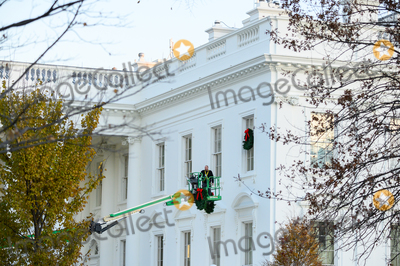 Donald Trump, White House, The White Photo - A worker hangs Christmas wreaths on the White House windows in Washington, DC on Monday, November 25, 2019. 