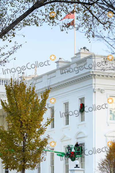 Donald Trump, White House, The White Photo - A worker hangs Christmas wreaths on the White House windows in Washington, DC on Monday, November 25, 2019. Credit: Erin Scott / CNP/AdMedia
