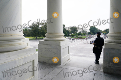 Police Officer Photo - A U.S. Capitol Police officer looks from the Capitol where the flag-draped casket of Justice Ruth Bader Ginsburg will arrive later to lie in state at the U.S. Capitol, Friday, Sept. 25, 2020, in Washington.