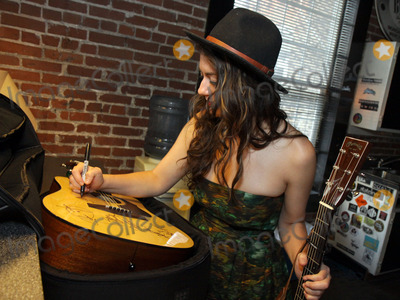Alyssa Bonagura, Pete Huttlinger Photo - July 26, 2011 - Nashville, TN - Alyssa Bonagura autographs a guitar later auctioned off. Artists, musicians and songwriters came together at Mercy Lounge to help raise funds for Pete Huttlinger, a widely respected guitarist and Nashville studio artist.  Huttlinger has a congenital heart disease and is in need of a heart transplant. Photo credit: Dan Harr/Admedia