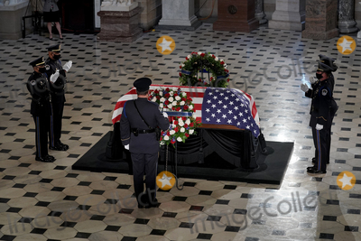 Photo - A U.S. Capitol Police honor guard salutes the late Justice Ruth Bader Ginsburg as she lies in state at National Statuary Hall in the U.S. Capitol on Friday, September 25, 2020. Ginsburg died at the age of 87 on Sept. 18th and is the first women to lie in state at the Capitol.