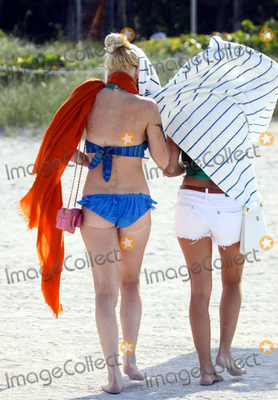 """Ali Lohan, Lindsay Lohan Photo - After enjoying a dip in the warm ocean, troubled American starlet Lindsay Lohan leaves the beach under cover with her entourage that includes younger sister Ali. Lohan's arm is covered in smudges from what looks like a fake tattoo, which looks like it reads """"blood,"""" that washed off in the water and her legs show signs of cuts and scarring. With her hair up, Lohan's hair extensions are clearly visible. Miami Beach, FL. 5/23/11.Fees must be agreed prior to publication."""