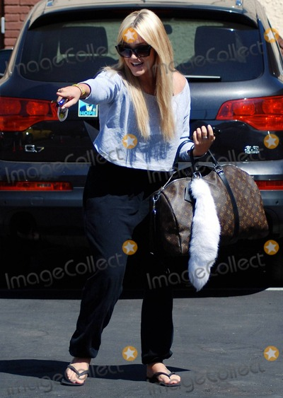 """Photo - Lacey Schimmer plays with a little dog as she leaves the """"Dancing with the Stars"""" studios after rehearsals for the upcoming season of the show which premieres September 20. Los Angeles, CA. 9/5/10."""