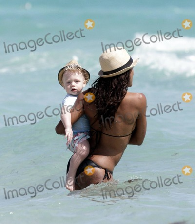 """Adored, Boris Becker, Fancy Photo - Sharlely Becker flashes her stellar figure in a bikini as her patterned sarong billows in the breeze while she spends some time at the beach with her adorable son Amadeus, decked out in his own snazzy straw fedora, and what appears to be the new nanny and another pal. Later Sharlely and husband Boris Becker, who was wearing a """"Fancy"""" t-shirt, his teenaged son Noah Becker's t-shirt label, went out together. Miami Beach, FL. 3/8/11."""