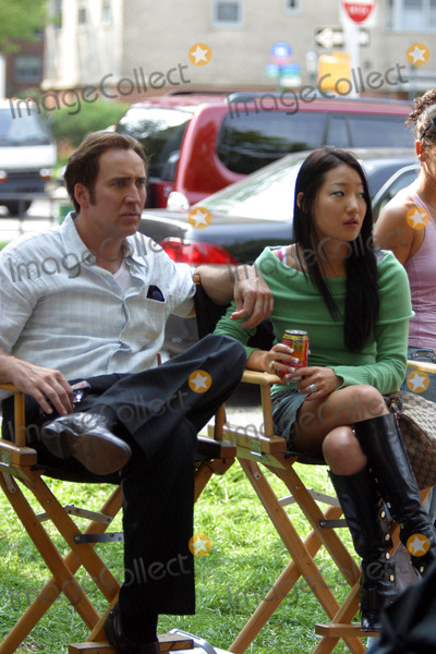 Alice Kim, Nicolas Cage, Nicolas Cazalé Photo - Actor Nicolas Cage chats with his new bride 20 year old ex-sushi waitress Alice Kim on the set of his new movie 'Lord of War' in which he plays an arms dealer. The scene was shot at a Jewish Temple in Brighton Beach, Brooklyn, New York City. August 3 2004.